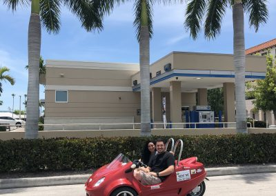 Couple drives by smiling in their scoot coupe on Marco Island