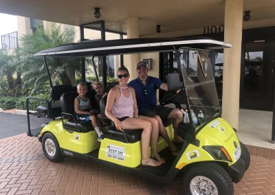 Family of 4 riding yellow golf cart on Marco Island