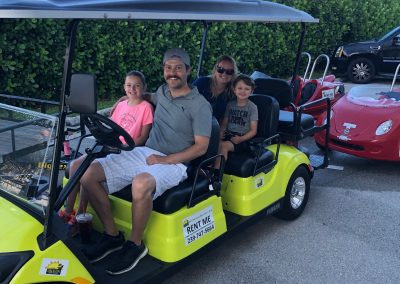Family riding golf cart in Marco Island