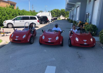 Family of 4 riding 3 red scoot coupes on marco island