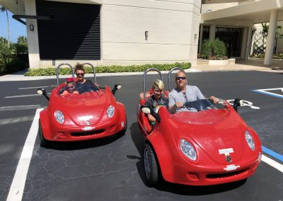Family of 4 riding two red scoot coupes on Marco Island