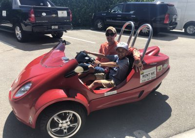 Father and son pose for picture on red scoot coupe on Marco Island