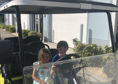 Two kids pretend to ride the yellow golf cart rental on Marco Island