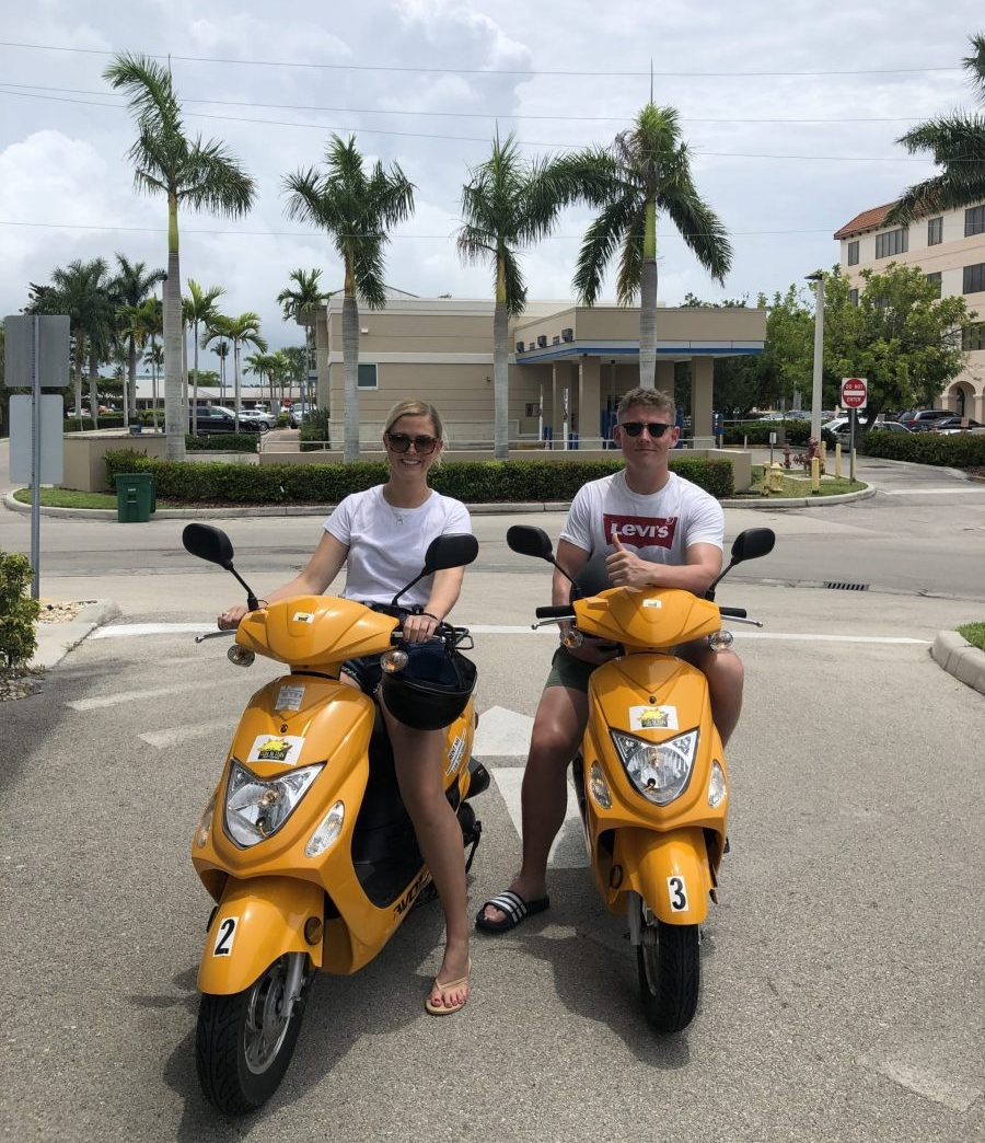 Couple riding two yellow scooters on Marco Island