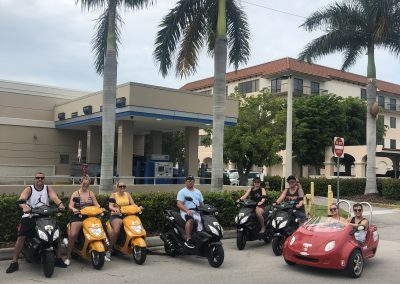 Big family poses for picture in scooters and scoot coupe on Marco Island