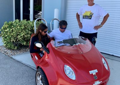 Couple riding red scoot coupe next to staff member in Marco Island