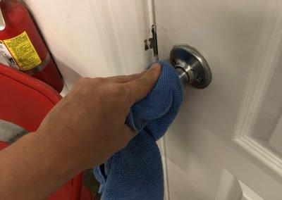 Sun-N-Fun staff member disinfecting door handle