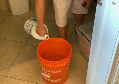 Sun-N-Fun staff member filling a bucket full of bleach