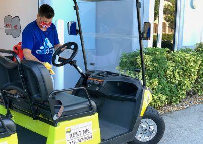Sun-N-Fun staff member cleaning a golf cart
