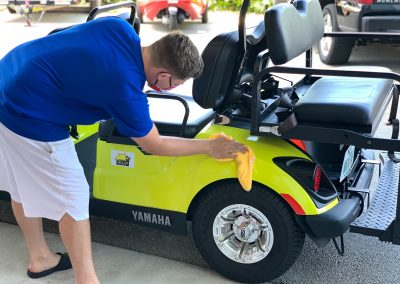 Sun N Fun staff member disinfecting a golf cart