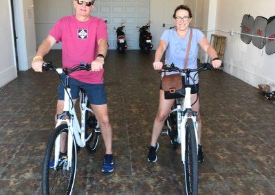Couple riding white e-bikes in the Sun-N-Fun garage