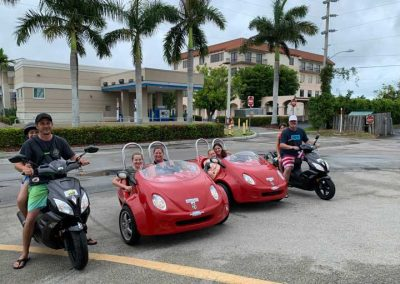 People renting and riding 2 black motor scooters and 2 red scoot coupes