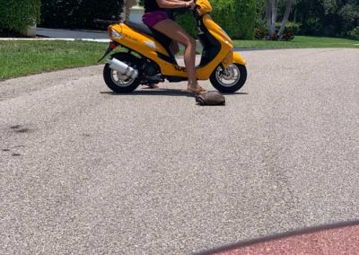 Woman riding a yellow motor scooter rental in Marco Island